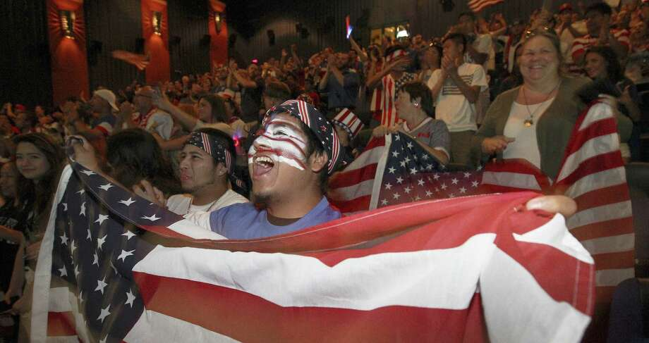 Rudy Rosales waves the U.S. flag as he joins hundreds of soccer fans at the Santikos Palladium IMAX theaters to watch the United States team play Belgium in the World Cup match on Tuesday. Photo: Kin Man Hui / San Antonio Express-News / ©2014 San Antonio Express-News