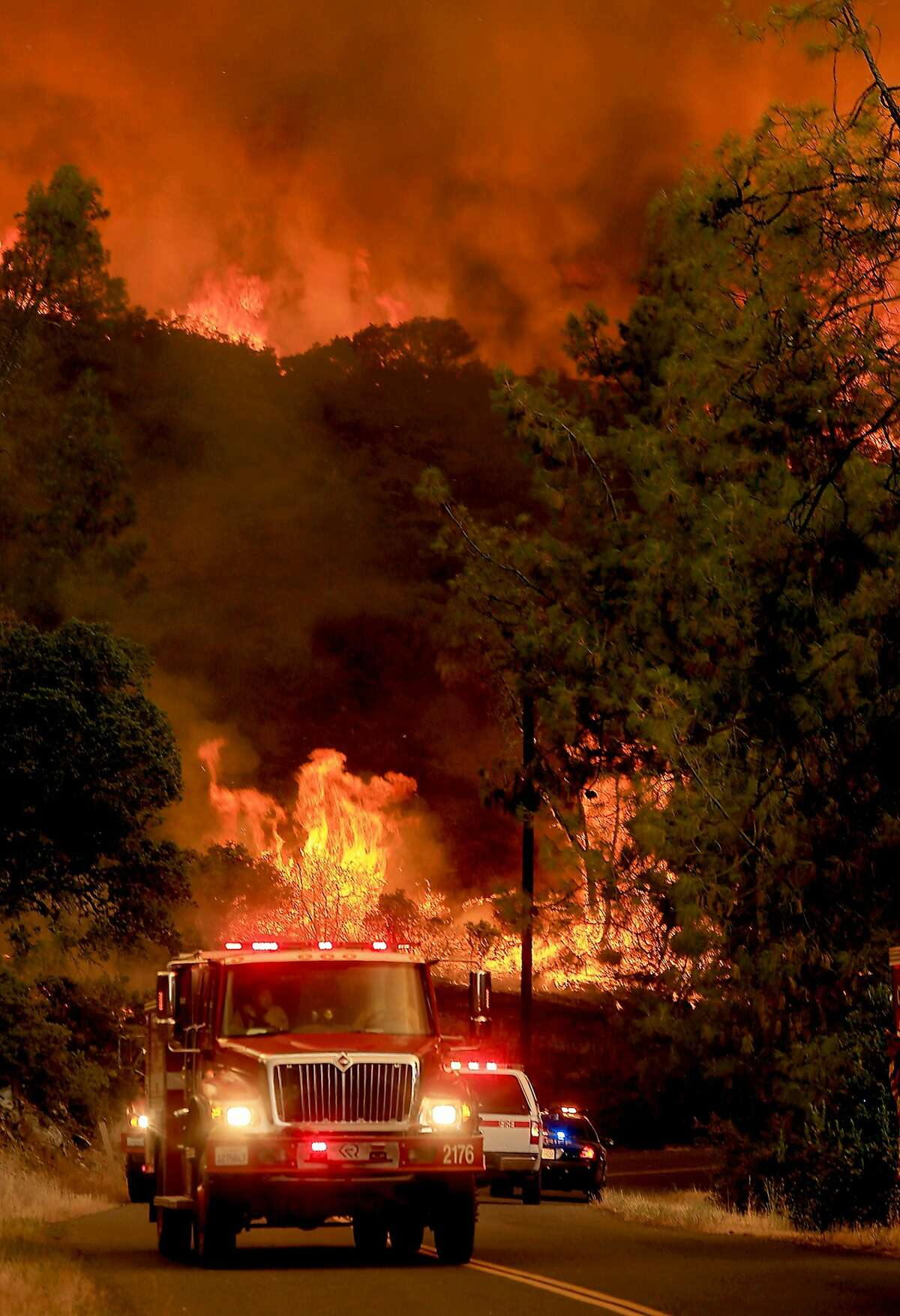 Fire personnel pull back from a wall of flames as it jumps Butts Canyon Road and Snell Valley Road, Tuesday, July 1, 2014, outside Middletown, Calif., near the border between Lake and Napa counties. By early evening 140 homes were evacuated and 2,500 acres were burned. (AP Photo/The Press Democrat, Kent Porter)
