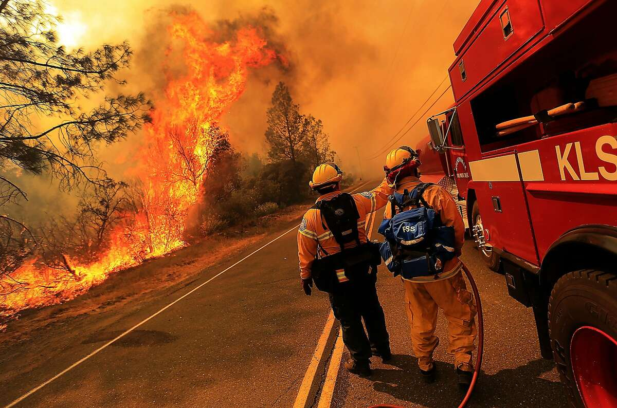 Kelseyville firefighters prepare to pull back from the fire on Butts Canyon Road, as the fire jumps the road, Tuesday July, 1, 2014, outside Middletown, Calif., at the border between Lake and Napa counties. By early evening 140 homes were evacuated and 2,500 acres were burned. (AP Photo/The Press Democrat, Kent Porter)