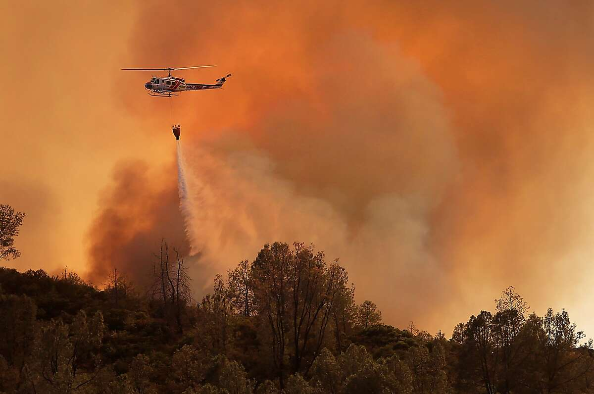A Cal Fire helicopter makes a drop on the Butts Canyon Fire on Tuesday, July 1, 2014, near Middletown, Calif., close to the border between Lake and Napa counties. By early evening 140 homes were evacuated and 2,500 acres were burned. (AP Photo/Santa Rosa Press Democrat, Kent Porter)