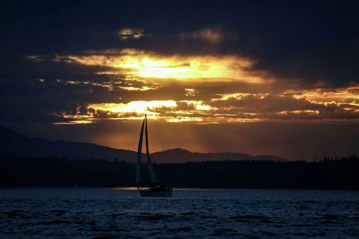 A sailboat floats through a sunbeam off of Golden Gardens.