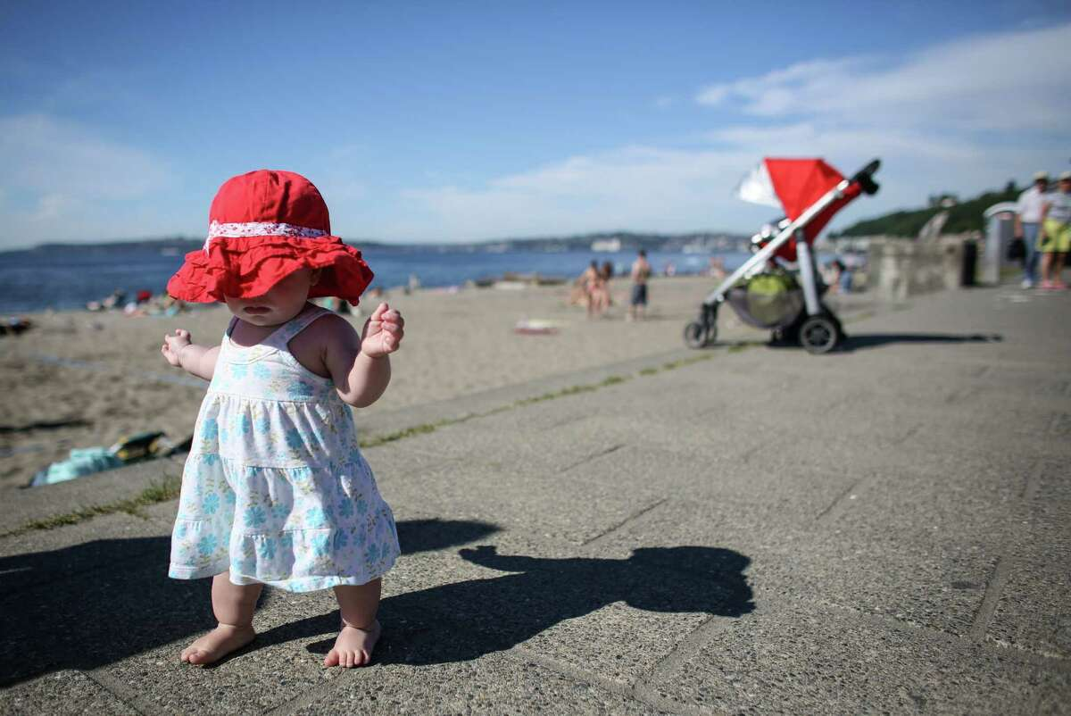 Madeleine Hebert, 12 months, walks with her family as people soak in the sun at Alki Beach.