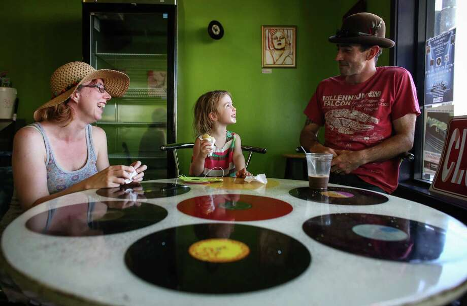 From left, Holly Csiga , Misha Csiga, 3, and Bryan Csiga enjoy ice cream at Full Tilt in White Center. Record-breaking temperatures brought people out to enjoy the Seattle summer sun —and inside to cool off. Photo: JOSHUA TRUJILLO, SEATTLEPI.COM / SEATTLEPI.COM