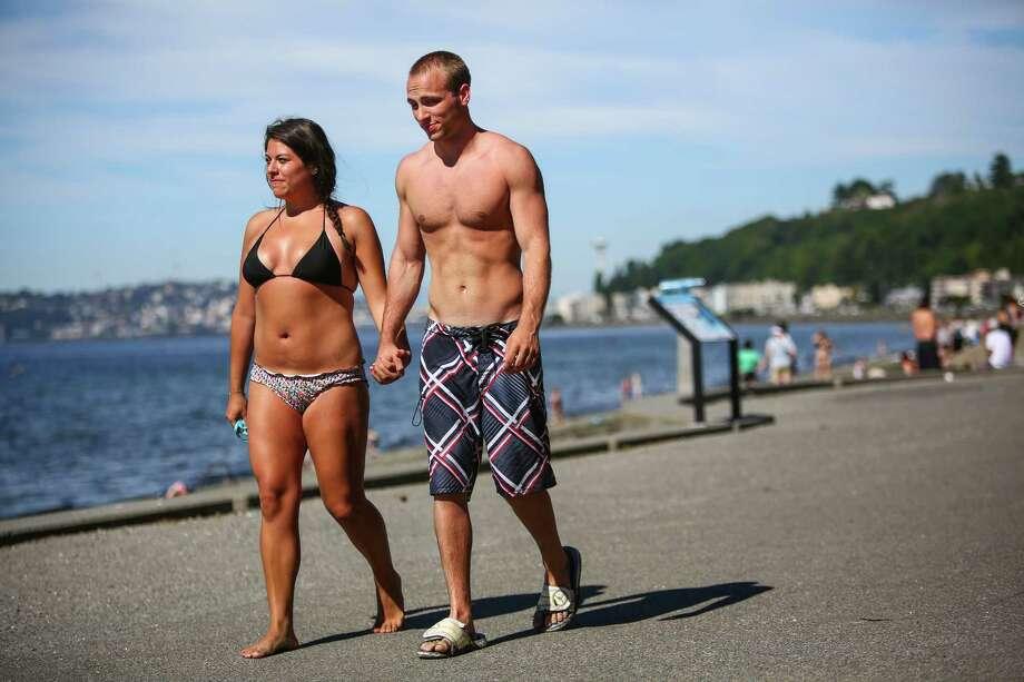 Maria Villavicencio and Matt Church walk at Alki Beach as people soak in the sun. Photo: JOSHUA TRUJILLO, SEATTLEPI.COM / SEATTLEPI.COM