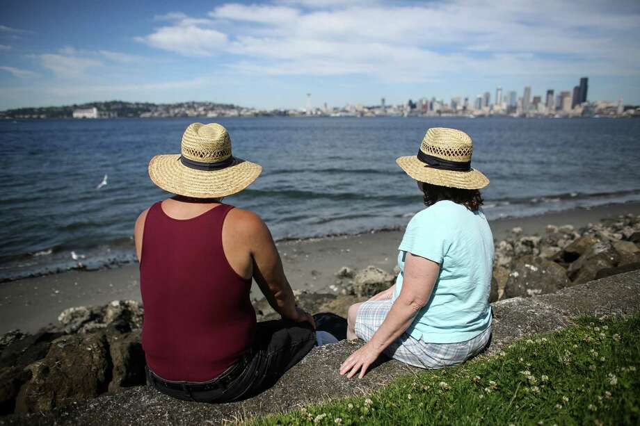 Patrick Shorter and Mary Sanders of Everett check out the skyline at Alki Beach, while getting some shade under hats. Photo: JOSHUA TRUJILLO, SEATTLEPI.COM / SEATTLEPI.COM