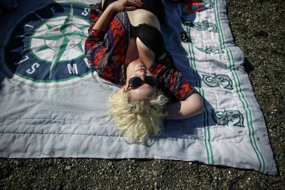 Alki resident Jayne Ashton relaxes on her Mariners blanket at Alki. Photo: JOSHUA TRUJILLO, SEATTLEPI.COM / SEATTLEPI.COM