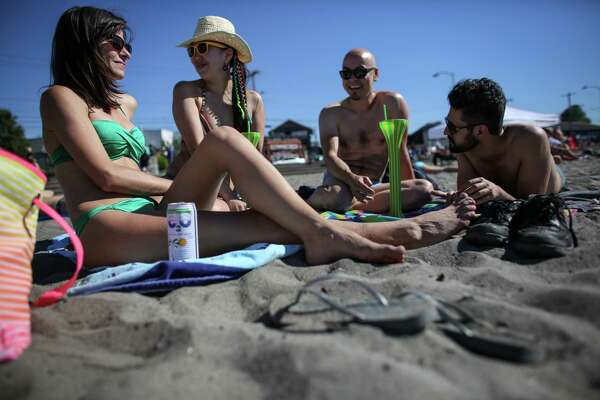 People gather on the sand at Alki Beach on Tuesday, July 1, 2014. Record-breaking temperatures brought people out to enjoy the Seattle summer sun.