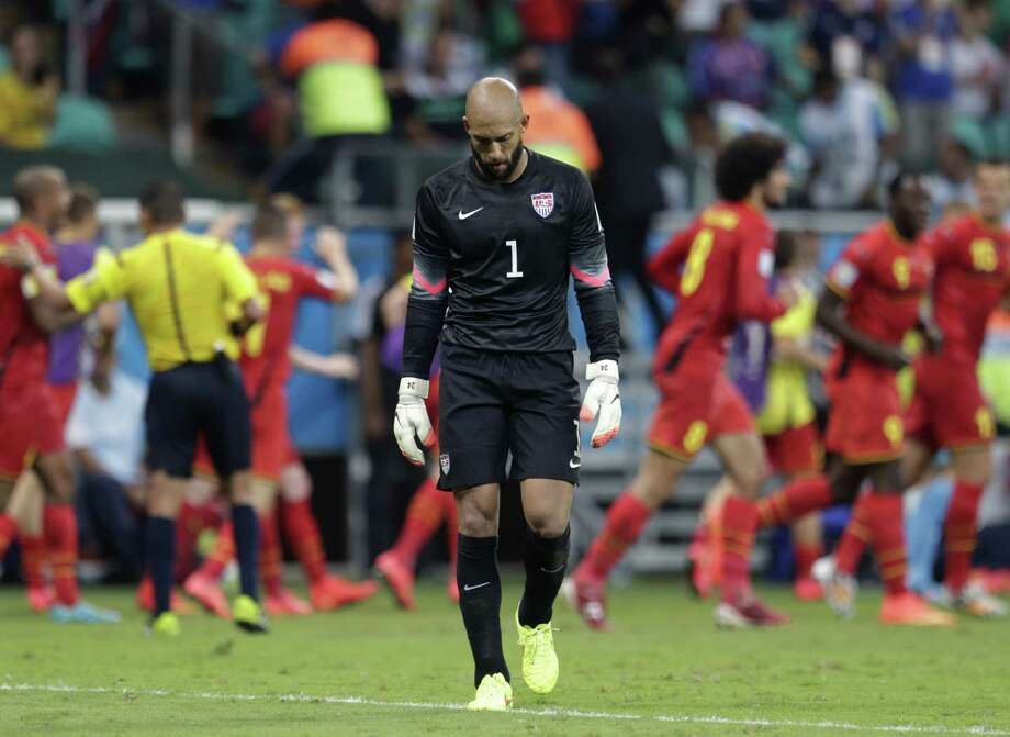 U.S. goalkeeper Tim Howard hangs his head as Belgium celebrates its first goal in extra time. Howard made 16 saves — the most recorded in a World Cup match in nearly 50 years — but two shots found the net late, and the Americans were unable to recover. Photo: Julio Cortez / Associated Press / AP