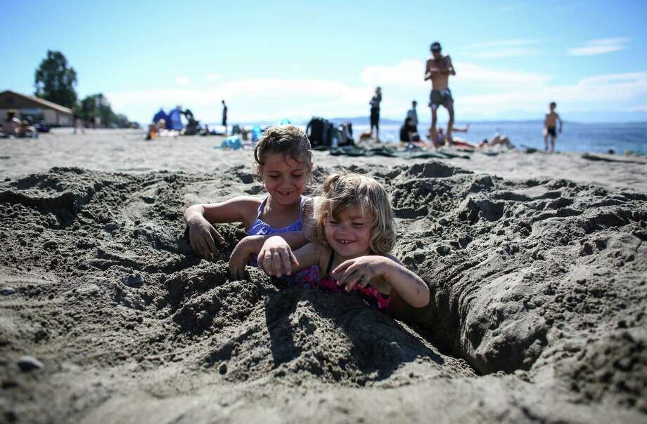 Cecilia Wisner, 6, Lucie Wisner, 3, cool off in the sand at Alki Beach. Photo: JOSHUA TRUJILLO, SEATTLEPI.COM / SEATTLEPI.COM
