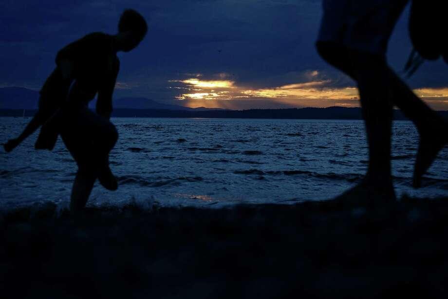 Beach-goers walk along the sands of Golden Gardens at dusk. Photo: JOSHUA BESSEX, SEATTLEPI.COM / SEATTLEPI.COM