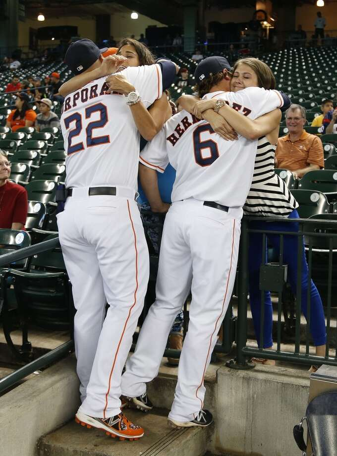 July 1: Mariners 13, Astros 2  Astros catcher Carlos Corporan (22) hugs newly brought up infielder Enrique Hernandez's dad as Hernandez hugs his mother, Monica Gonzalez. Photo: Karen Warren, Houston Chronicle