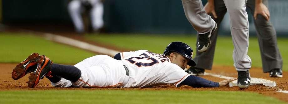 Astros second baseman Jose Altuve (27) dives back to first under Logan Morrison. Photo: Karen Warren, Houston Chronicle