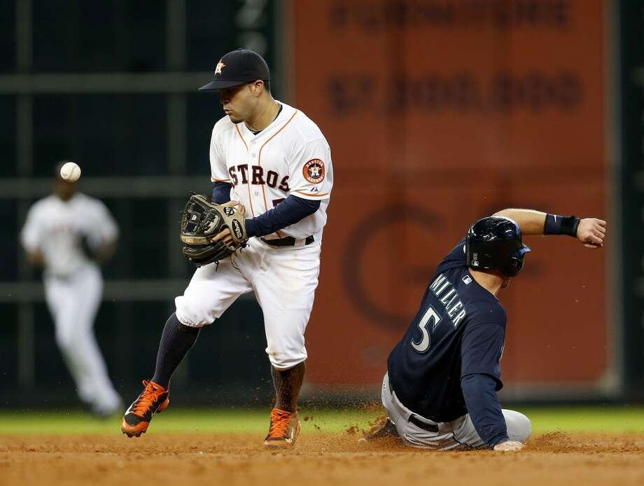 Astros second baseman Jose Altuve (27) tries to get his hands on a ball as he tags Brad Miller (5) out at second. Photo: Karen Warren, Houston Chronicle