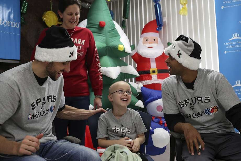 Spurs players Manu Ginobili, left, and Patty Mills visit patients including Luke Baca, 5, with his mother, Janelle Baca, at Children's Hospital of San Antonio on Friday, Dec. 6, 2013. Photo: Lisa Krantz, San Antonio Express-News