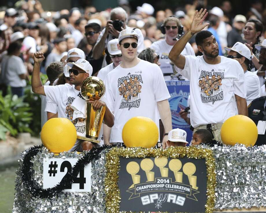 San Antonio Spurs' Patty Mills (from left), Aron Baynes, and Tim Duncan react Wednesday June 18, 2014 during the river parade for the San Antonio Spurs after the team captured their fifth NBA championship. Photo: Edward A. Ornelas, San Antonio Express-News