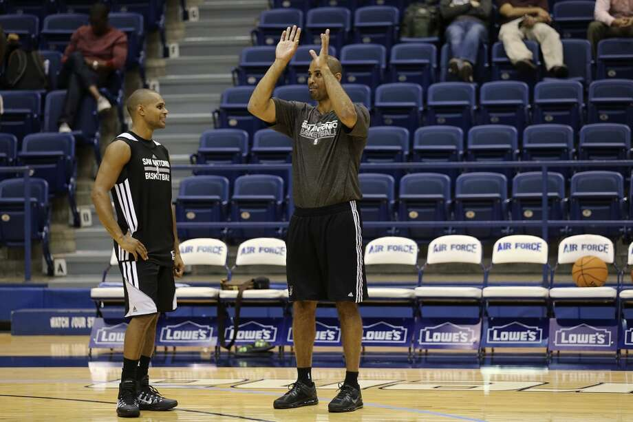 San Antonio Spurs guard Patty Mills, left, talks with assistant coach Ime Udoka during practice at Clune Arena of the United State Air Force Academy in Colorado Springs, Colorado, Tuesday, Oct. 1, 2013. Photo: Jerry Lara, San Antonio Express-News