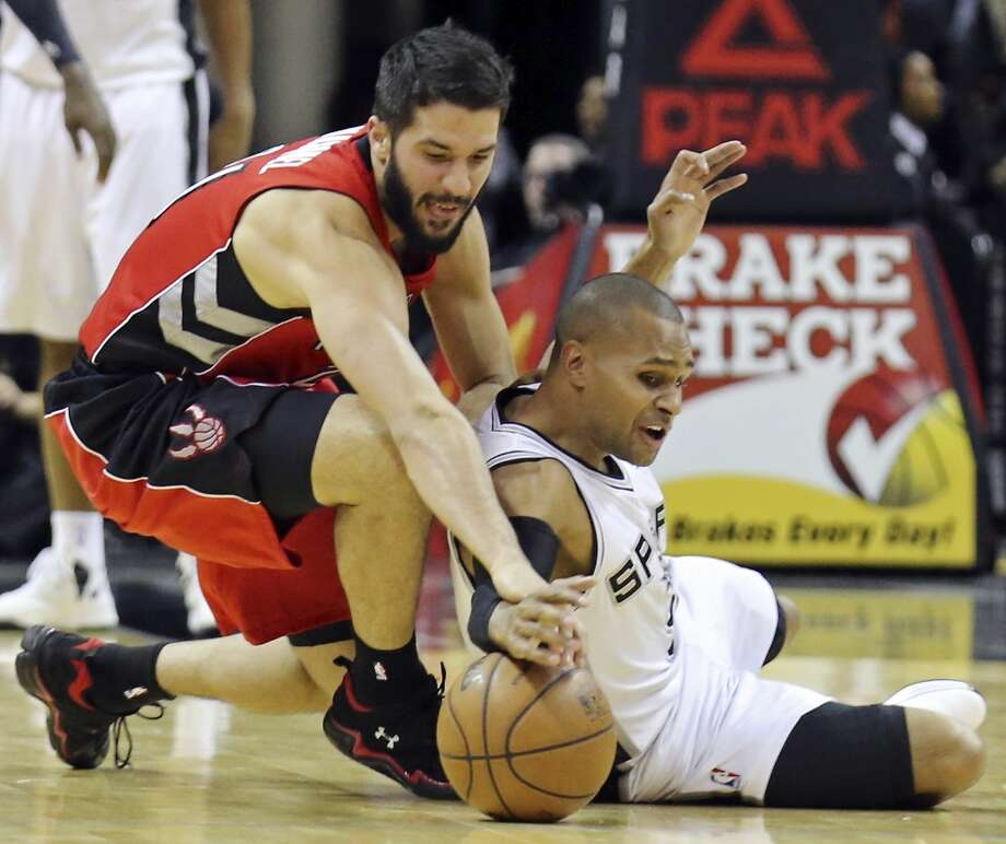 San Antonio Spurs' Patty Mills and Toronto Raptors' Greivis Vasquez chase after a loose ball during second half action Monday Dec. 23, 2013 at the AT&T Center. The Spurs won 112-99. Photo: Edward A. Ornelas, San Antonio Express-News