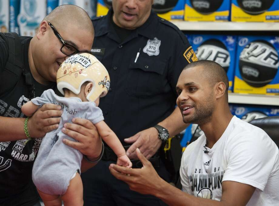 San Antonio Spurs guard Patty Mills, right, of Australia, greets Anthony Allsup, left, and his nine-month-old son, Ethan, on Saturday, June 21, 2014, at the Bandera/1604 H-E-B in San Antonio. (Darren Abate/For the Express-News) Photo: Darren Abate, Darren Abate/Express-News