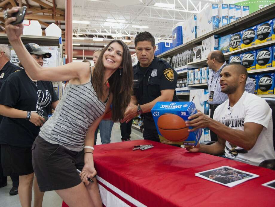 Michelle Cabezas, left, who drove from Houston for the event, takes a selfie after getting an autograph from San Antonio Spurs guard Patty Mills on Saturday, June 21, 2014, at the Bandera/1604 H-E-B in San Antonio. (Darren Abate/For the Express-News) Photo: Darren Abate, For The Express-News