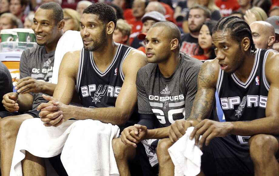 San Antonio Spurs' Boris Diaw (from left), Tim Duncan, Patty Mills, and Kawhi Leonard watch late second half action of Game 3 in the Western Conference semifinals against the Portland Trail Blazers from the bench Saturday May 10, 2014 at the Moda Center in Portland, OR. The Spurs won 118-103. Photo: Edward A. Ornelas, San Antonio Express-News