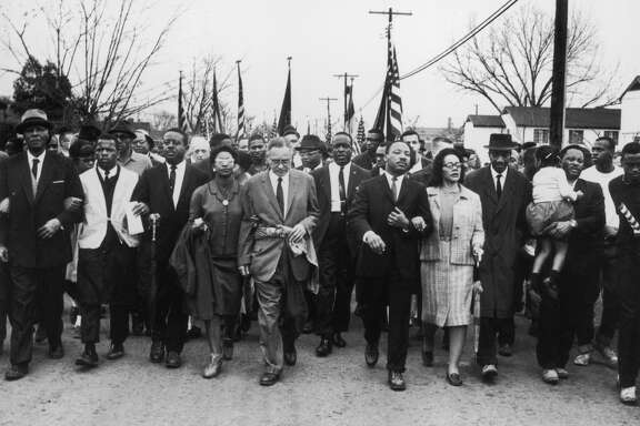 American civil rights campaigner Martin Luther King and his wife Coretta Scott King lead a black voting rights march from Selma, Alabama, to the state capital in Montgomery o March 30, 1965.