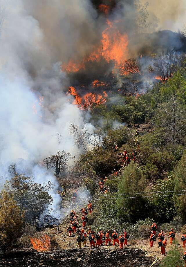 A crew heads back downhill as flames advance up a hillside on the Butts Canyon Fire, Tuesday, July 1, 2014, outside Middletown, Calif., on the border between Lake and Napa counties. By early evening 140 homes were evacuated and 2,500 acres were burned.  Photo: Kent Porter, Associated Press