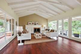 The living room hosts a vaulted, beamed ceiling and French doors opening to a covered patio.