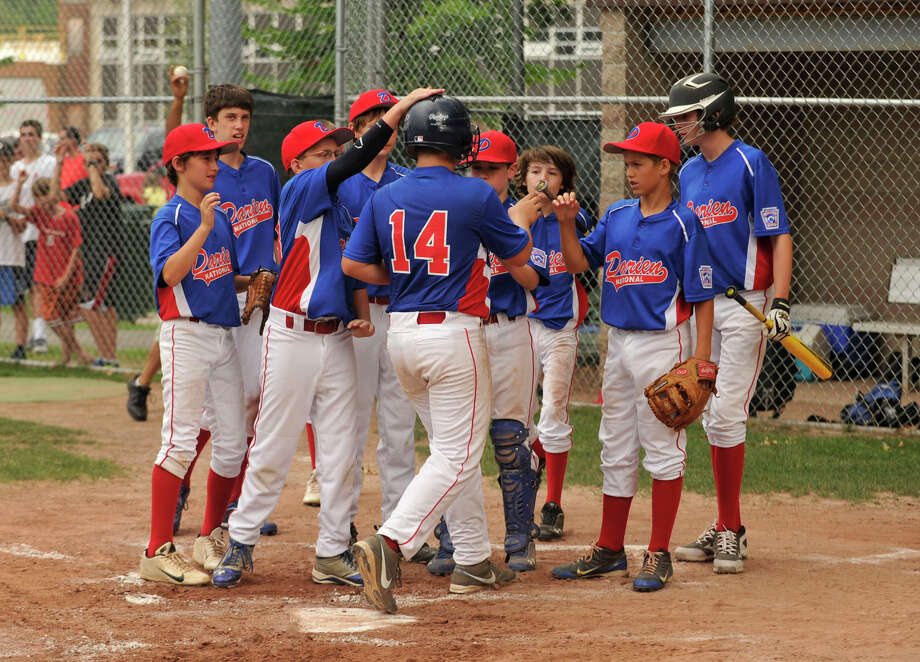 The Darien National team celebrates after Sean O'Malley(14)  hit a home run during their District 1 Little League semifinal game against Wilton at Scalzi Park in Stamford on Tuesday, July 9, 2013. Photo: Jason Rearick / Stamford Advocate