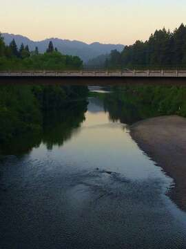 A river runs through it:  Twilight adds a tranquil cast to the Russian River, as seen looking west from the Guerneville Bridge. To the east lies  Johnson's Beach , which bustles in the summer with sunbathers, kayakers, swimmers and others drawn to the shallow but cold water. Founded in 1918, the family-owned campground and resort attracts a diverse crowd typical of Guerneville.