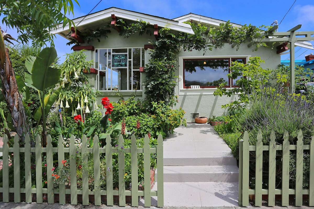 A picket fence wraps around the established garden in front of the Berkeley home.