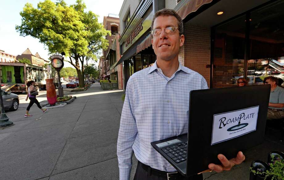 Zack Vogel looks out on to Broadway in Saratoga Friday morning June 27, 2014, in Saratoga Springs, N.Y.  Vogel has developed a new website, focused on Saratoga at the moment, as a central place for people to see daily specials at restaurants.   (Skip Dickstein / Times Union) Photo: SKIP DICKSTEIN / 00027513A