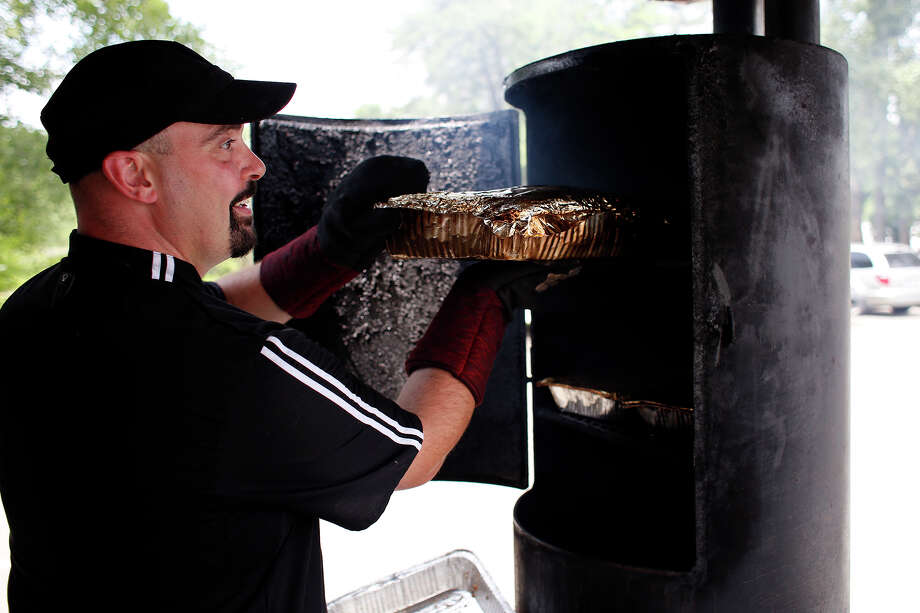 Chef Joe Reilly prepares a tray of ribs inside of a wood-fired smoker, attached to the Stockyard Bar-B-Q And Catering truck, stationed at 114 Railroad Avenue on Monday, June 30, 2014, in Albany, N.Y.  (Tom Brenner/ Special to the Times Union) Photo: Tom Brenner / ©Tom Brenner/ Albany Times Union
