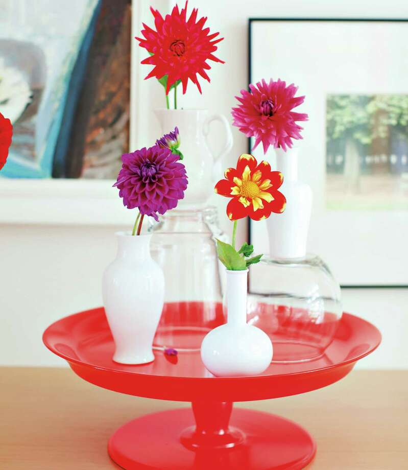 """In this image from """"Decorate with Flowers,"""" the authors recommend playing with scale and placing vases on top of stacked books, cake stands or anything to elevate them. Photo: Photo Courtesy Chronicle Books / Copyright: janis nicolay photography 2011"""