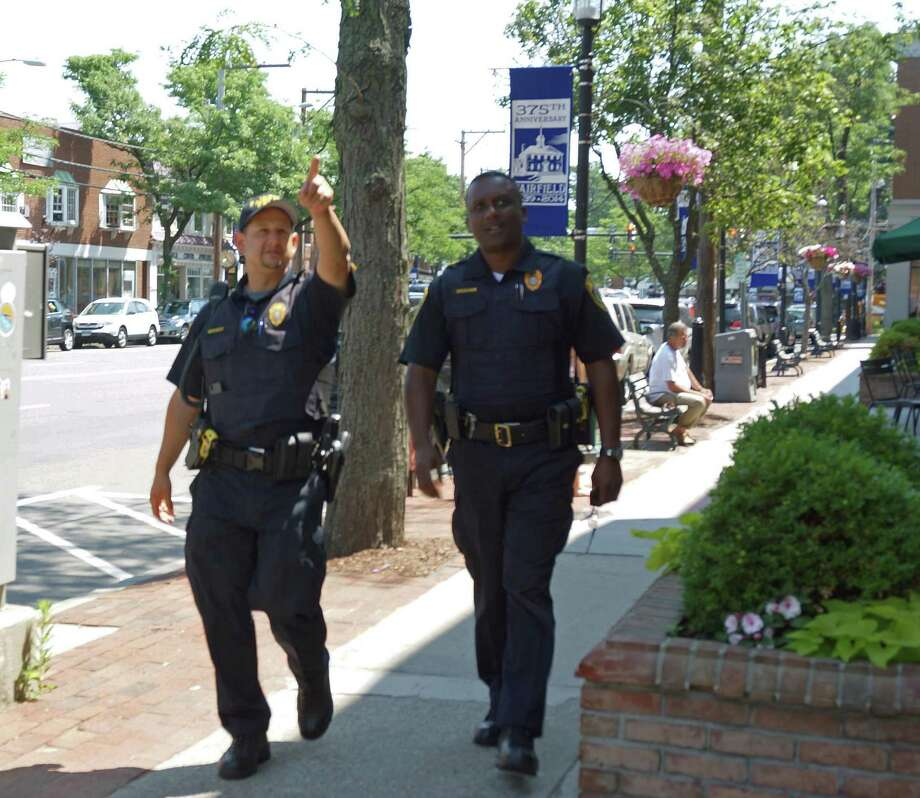 Officers Paul Medvegy, left, and Robert Braham, take to the sidewalk as part of a new pilot program for the downtown business community. Photo: Genevieve Reilly / Fairfield Citizen