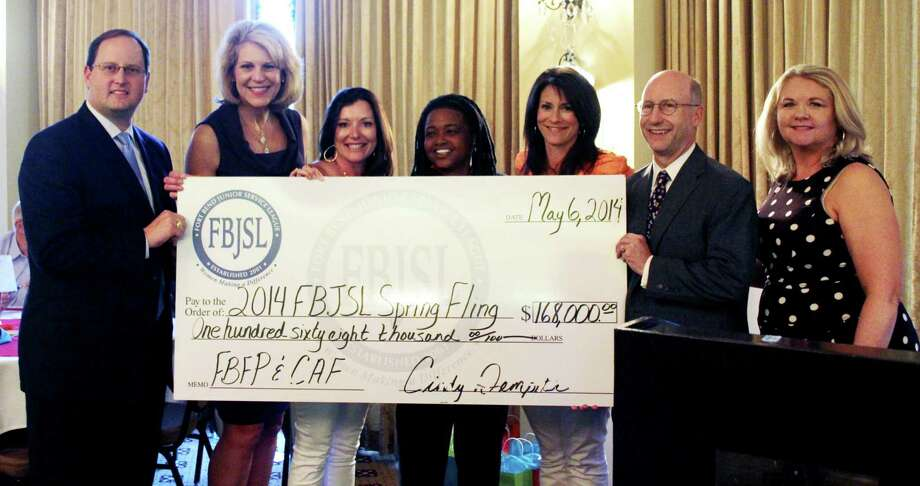 Participating in the check presentation to Family Promise were, from left, Greg Haralson, Memorial Hermann Sugar Land Hospital chief executive officer; Nancy Olson, Fort Bend Family Promise board member and Spring Fling honorary chair; Johnnie Wright, Spring Fling co-chair; Vera Johnson, Fort Bend Family Promise executive director; Melissa Hayslip, Spring Fling co-chair; John Tipton, Fort Bend Family Promise board president; Cindy Dempster, FBJSL board president. Not shown is KK West, Spring Fling co-chair. Photo: Courtesy Fort Bend Junior Service League