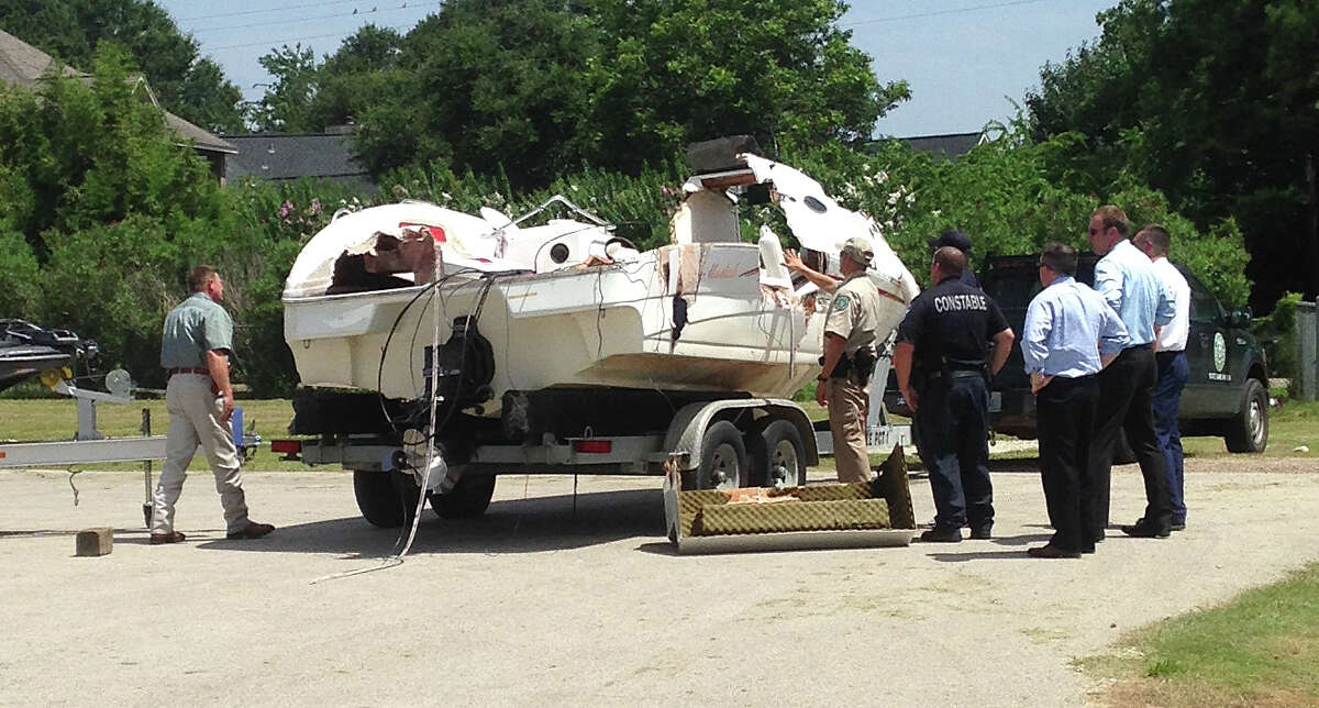 Investigators on Wednesday examine a pleasure boat that was involved in collision with a bass boat on Lake Conroe on Tuesday night. The collision killed a woman who was onboard the pleasure boat and left another woman missing. A 9-year-old boy died Wednesday morning at a Houston hospital of injuries sustained in the accident. Seven others were hurt. The bass boat is shown on the left. Photo: Cindy Horswell