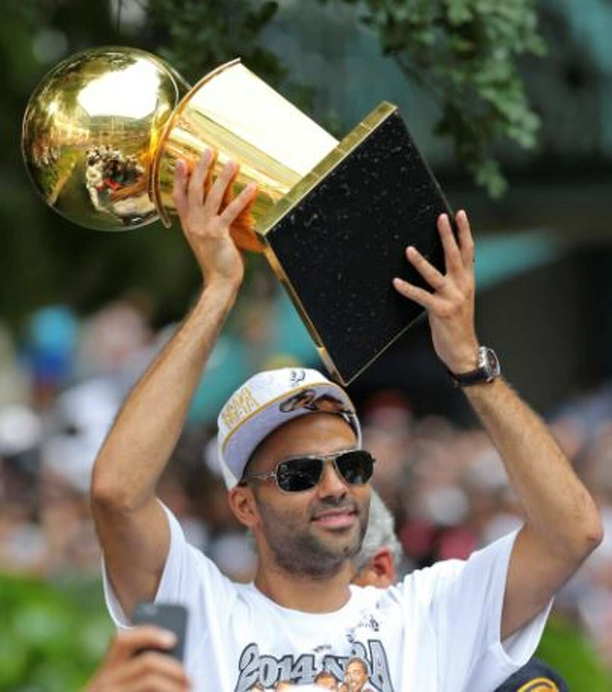 Tony Parker holds one of the five Larry O'Brien trophies the Spurs have won duirng the Championship Celebration on the River Walk.