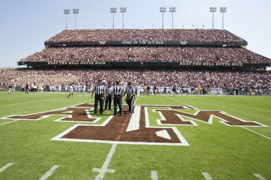 Officials meet at midfield before the 2013 season opener against Rice. Photo: Brett Coomer, Houston Chronicle
