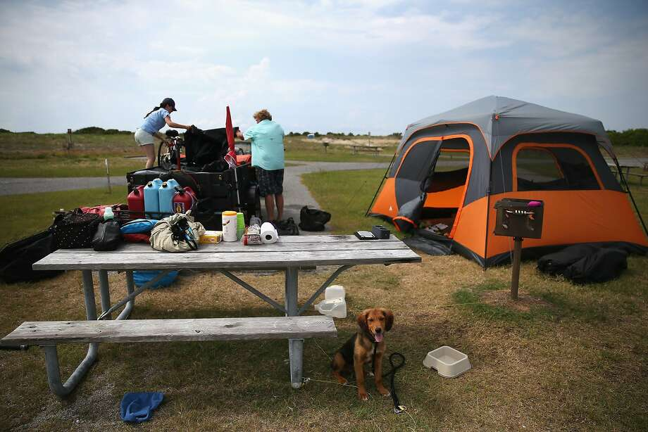 Hannah Thomas and Scott Brooks of Boston break down their campsite in Oregon Inlet, N.C., as Cape Hatteras National Seashore ordered evacuations. Photo: Mark Wilson, Getty Images