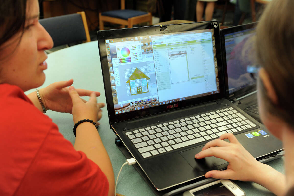 Ana Campos, left, and Emily Troll work on their teamís mobile app, part of the CT Pre-Engineering Program (CPEP) summer design program at Danbury High School, in Danbury, Conn. July 2, 2014. CPEP students are spending the summer developing and designing mobile apps.
