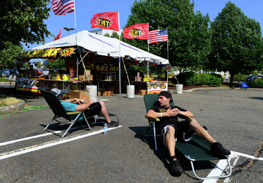TNT Fireworks employees Phil Douglas and Zack Spescha, left, sit in the parking lot of the Connecticut Post Mall waiiting for customers to buy fireworks in Milford, Conn. on Tuesday July 1, 2014. All legal fireworks in the state must be stationary, or called a fountain, in which all the fireworks never leave the ground. Any that do are considered illegal in the hands of consumers. Photo: Christian Abraham / Connecticut Post
