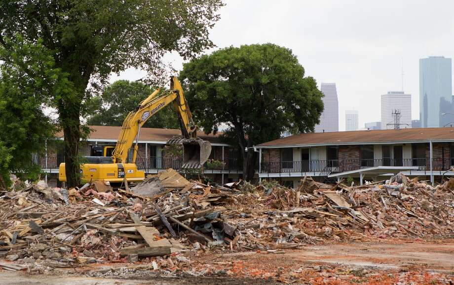 A crew demolishes the Skylane apartments in the 2200 block of White Oak, Wednesday, July 2, 2014. Photo: Cody Duty, Houston Chronicle