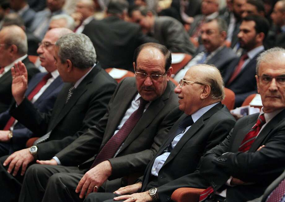 Prime Minister Nouri al-Maliki (center) talks with Supreme Court chief Midhat al-Mahmoud during a parliamentary session. Sunni and Kurdish politicians have refused to accept his bid for a third term. Photo: Ahmad Al-rubaye, AFP/Getty Images