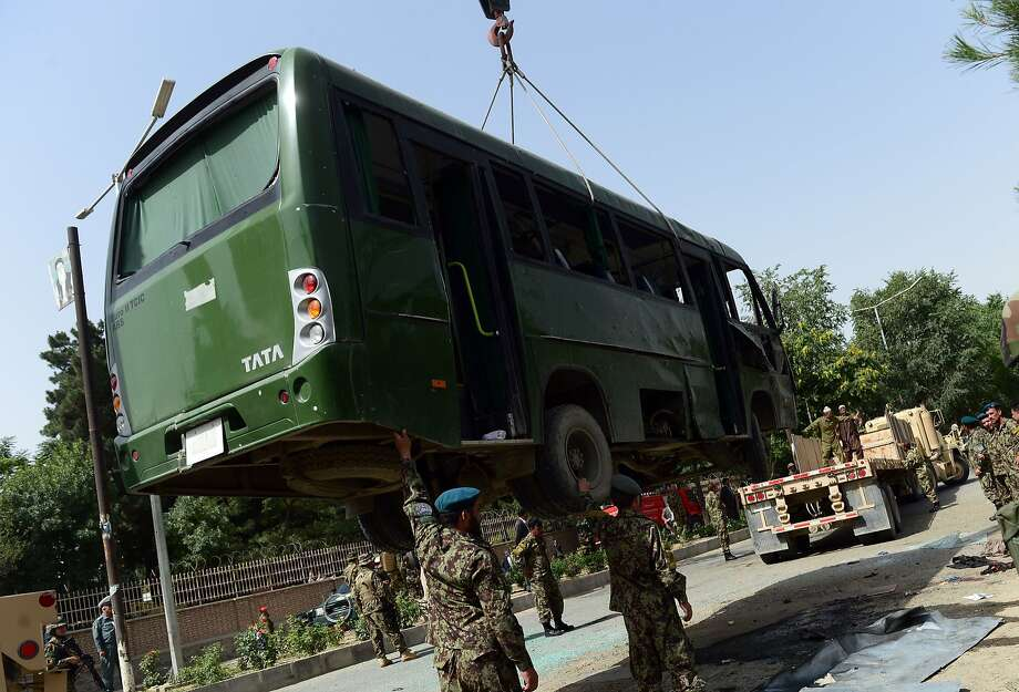 Afghan soldiers lift a damaged military bus with a crane after a suicide attack in Kabul. Photo: Wakil Kohsar, AFP/Getty Images