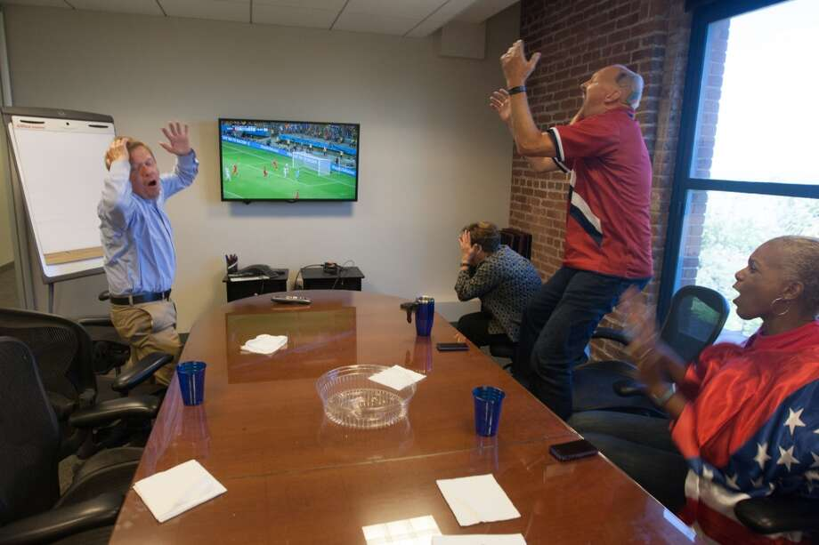 In the second half, several employees at Arthur J. Gallagher insurance company took over a small meeting room to watch the game. They reacted when the USA just missed a goal moments before the end of regulation. Photo: Douglas Zimmerman, Courtesy
