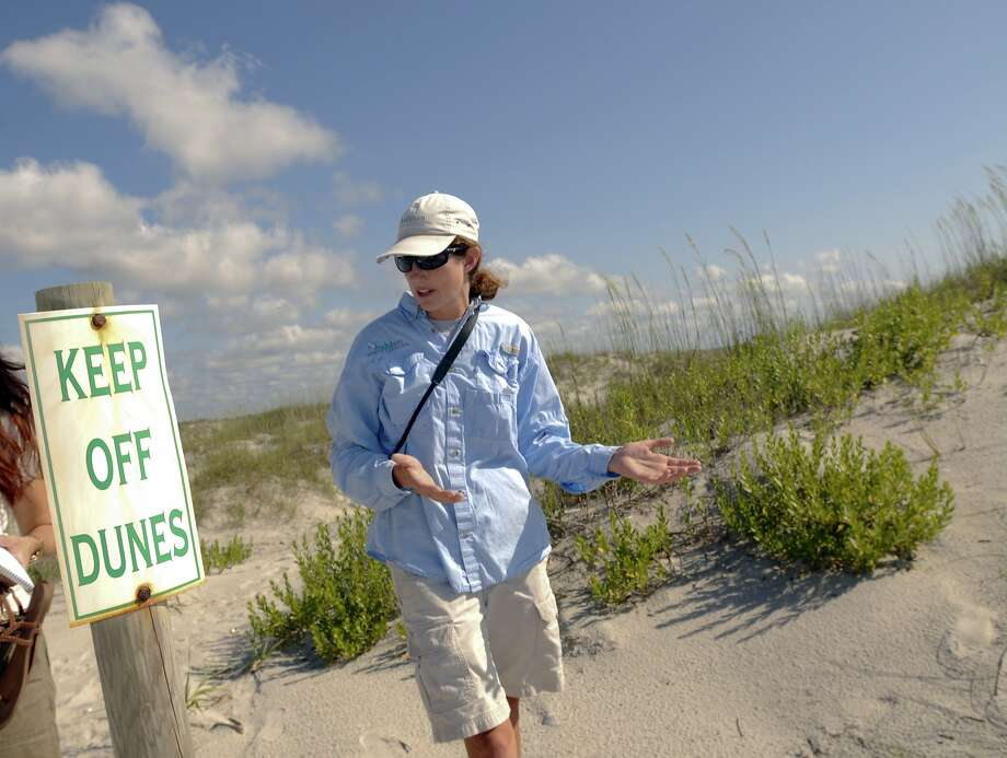Except for bird experts: Lindsay Addison, coastal biologist with Audubon North Carolina, walks the perimeter of sensitive bird-nesting grounds at the north end of Wrightsville Beach, N.C. Photo: Mike Spencer, Associated Press