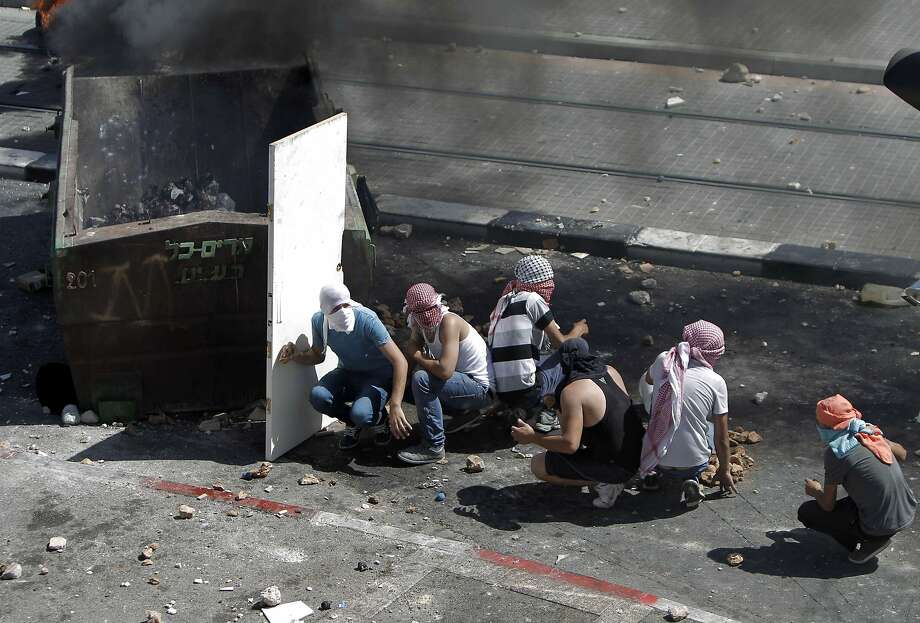Don't open the door:Palestinian protesters take cover during clashes with Israeli police in the Shuafat neighborhood of Israeli-annexed Arab East Jerusalem. The violence began after a Palestinian teenager was kidnapped and killed in an apparent act of revenge for the murder of three Israeli youths  by militants. Photo: Ahmad Gharabli, AFP/Getty Images