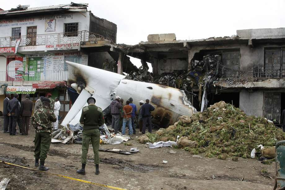 Deadly plane crash:Soldiers and airport staff members inspect the wreckage of a Fokker 50 cargo plane that crashed into a building during takeoff at Kenyatta International Airport in Nairobi. Four crew members were killed when the plane, which was transporting the mild stimulant drug khat to the Somali capital of Mogadishu, went down. Photo: Khalil Senosi, Associated Press