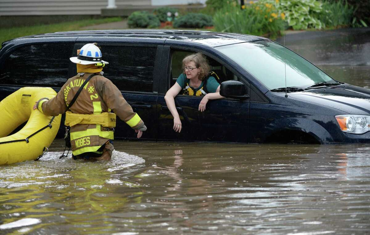 A Niskayuna firefighter returns for the second of two trapped in a flooded vehicle Wednesday afternoon, July 2, 2014, on Merlin Drive in Niskayuna, N.Y. A furious afternoon storm flooded roads, tore down trees, knocked out power to thousands and stranded motorists across the Capital Region. (Skip Dickstein / Times Union)