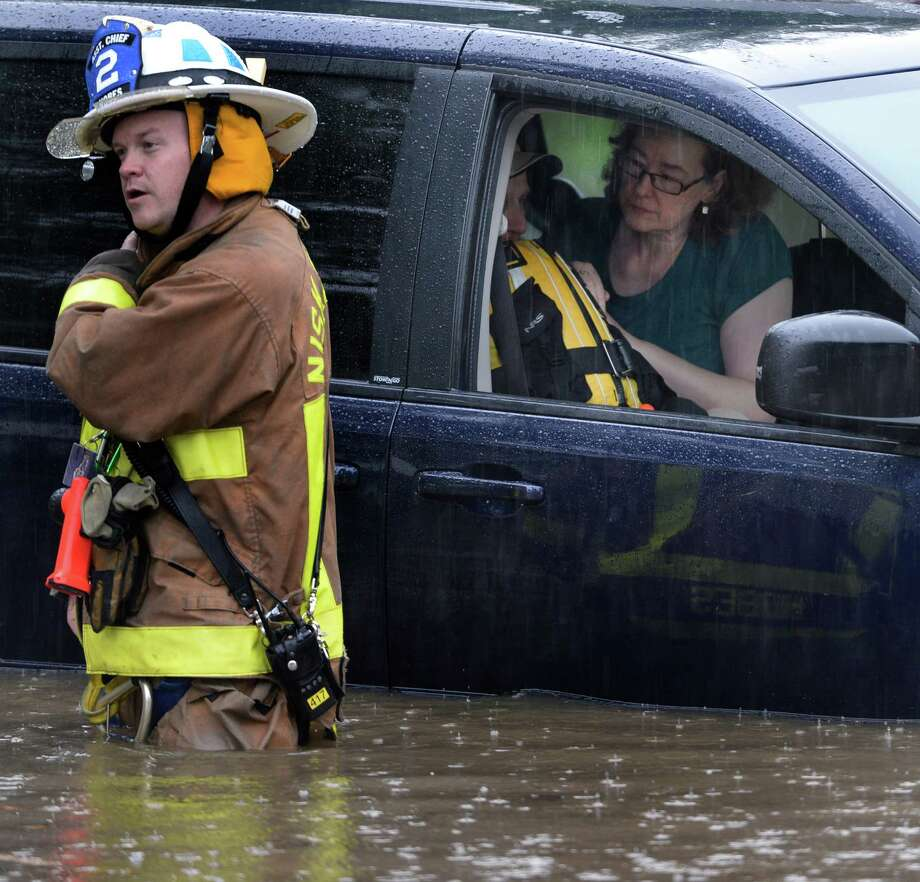 A woman comforts a stranded passenger while waiting for Niskayuna firefighters to rescue them from their flooded vehicle Wednesday afternoon, July 2, 2014, on Merlin Drive in Niskayuna, N.Y. A furious afternoon storm flooded roads, tore down trees, knocked out power to thousands and stranded motorists across the Capital Region. (Skip Dickstein / Times Union) Photo: SKIP DICKSTEIN